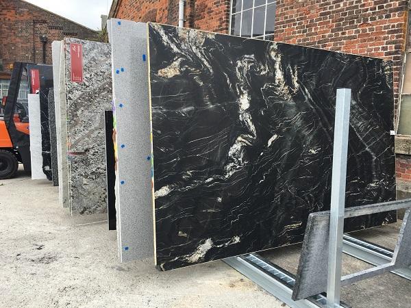 large granite slabs in a rack - cost of granite worktops versus cost of quartz worktops