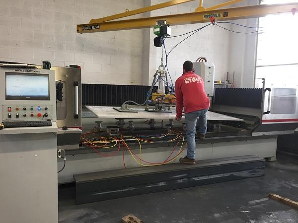 Alex loading quartz slab into CNC machine - cost of granite worktops versus cost of quartz worktops
