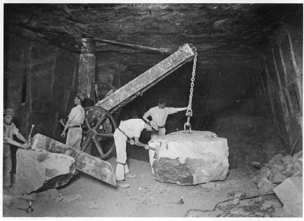large block of limestone being held up on crane in under ground bath stone quarry