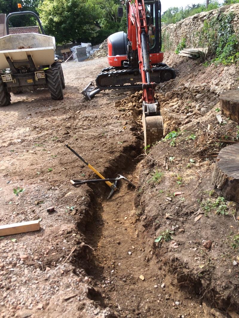 Excavating footings for vertical sleeper retaining wall