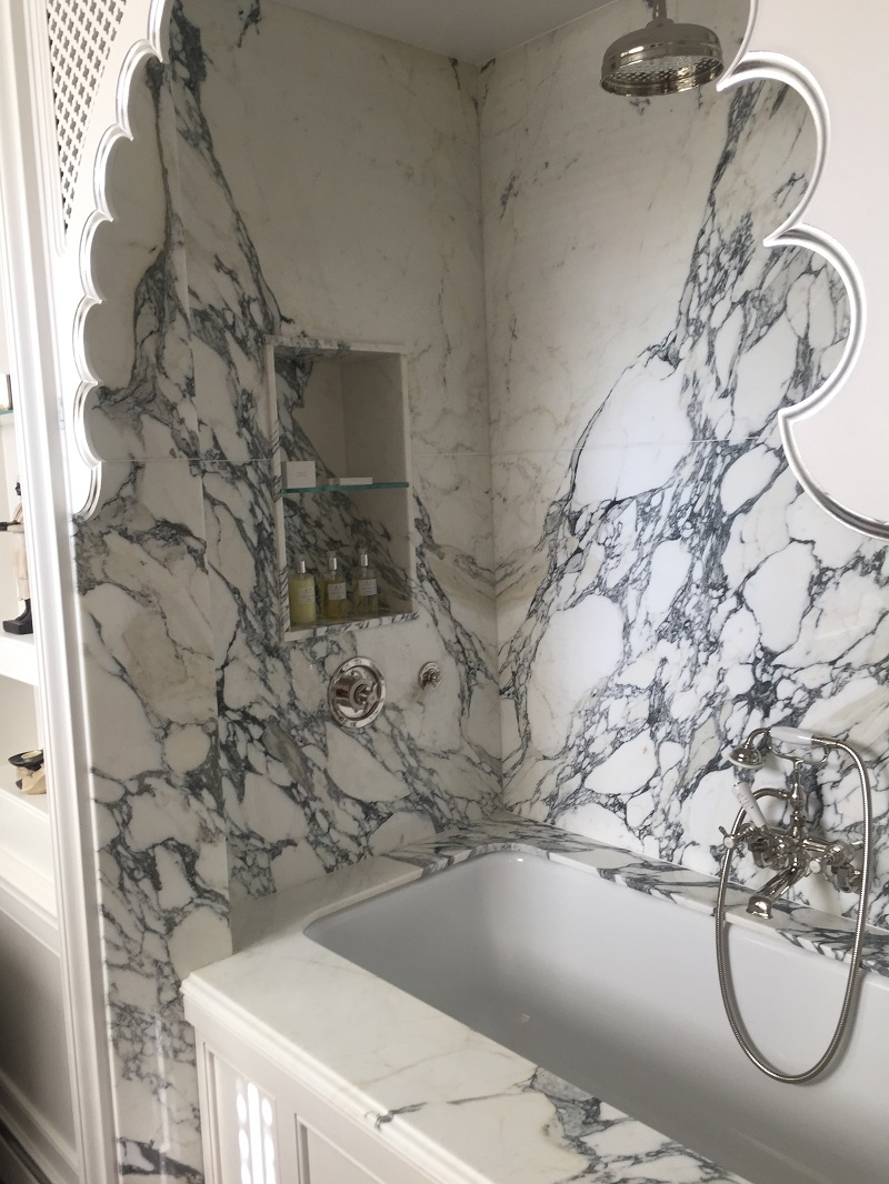 book match marble wall cladding behind a stone splash back by Everything Stone